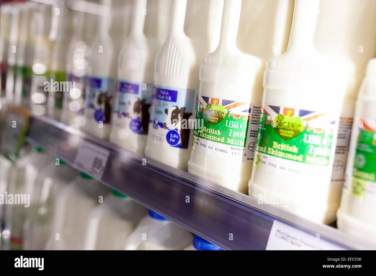 Le bottiglie di plastica del latte in frigorifero a un supermercato Morrisons Immagini Stock