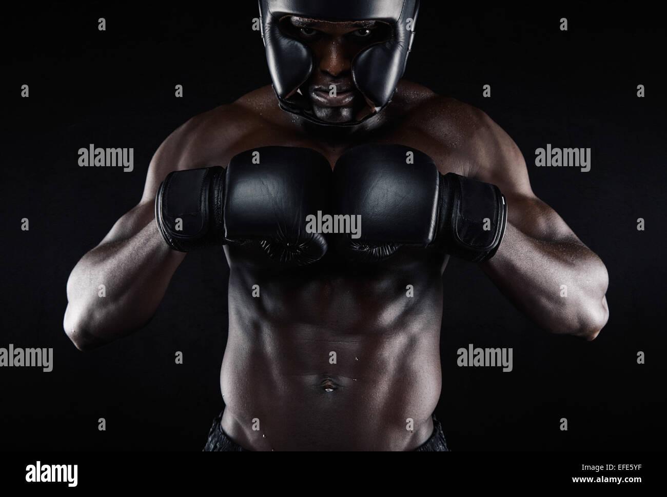 Ritratto di giovane africano boxer maschio di preparare per la concorrenza su sfondo nero. Muscoloso maschio modello Immagini Stock