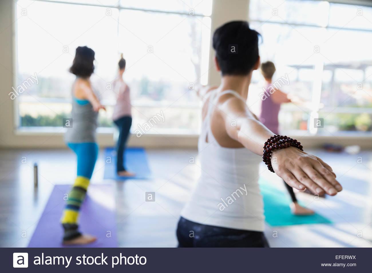 Le donne praticanti warrior 2 pone in classe di yoga Immagini Stock