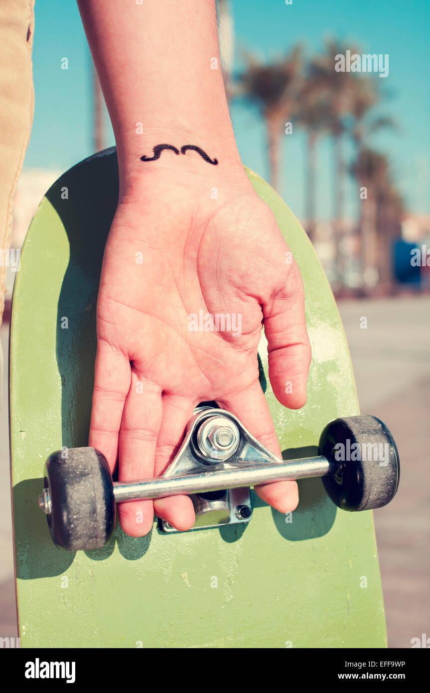 Primo piano di un giovane uomo con i baffi tatuati nel suo polso tenendo uno skateboard Immagini Stock