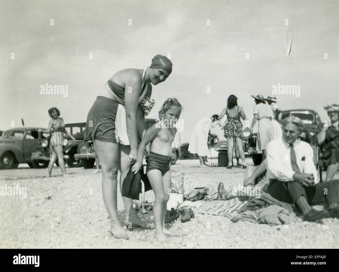 Il 12 Dic. 2014 - Canada - circa trenta: Riproduzione di un antico mostra fotografica di una donna in costume da bagno e un cappuccio di gomma mette una bambina sulla spiaggia, guardando loro anziani imprenditore in un tirante, nessuna camicia che siede accanto alla sabbia. Sullo sfondo una donna in costume da bagno e un vestito e hat contro lo sfondo di automobili. (Credito Immagine: © Igor Golovniov/ZUMA filo/ZUMAPRESS.com) Foto Stock