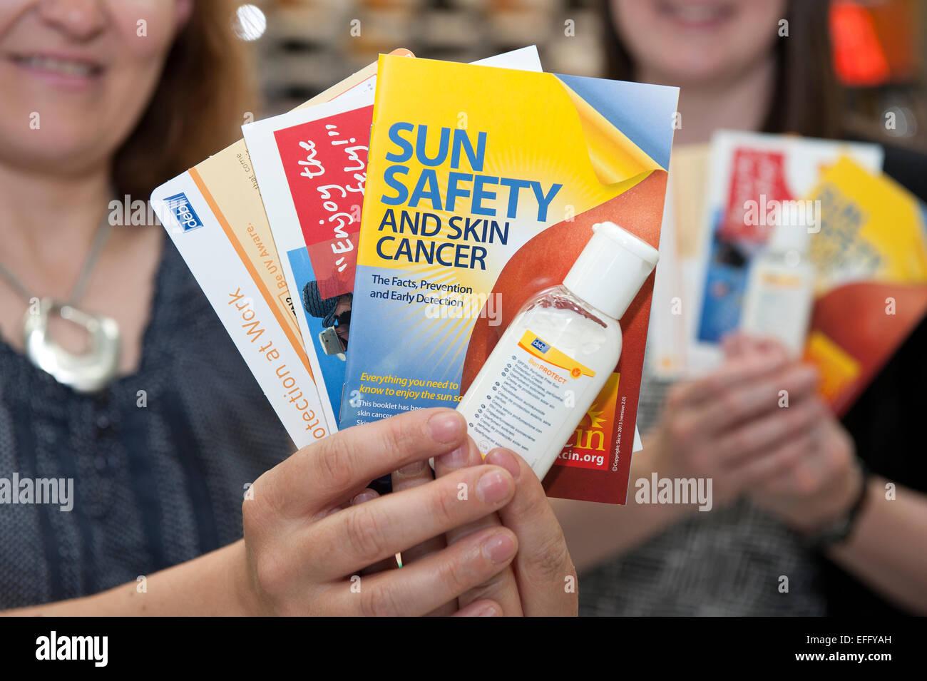 Due donne non identificato hold up volantini di sicurezza e crema solare le avvertenze sui pericoli di cancro alla Immagini Stock