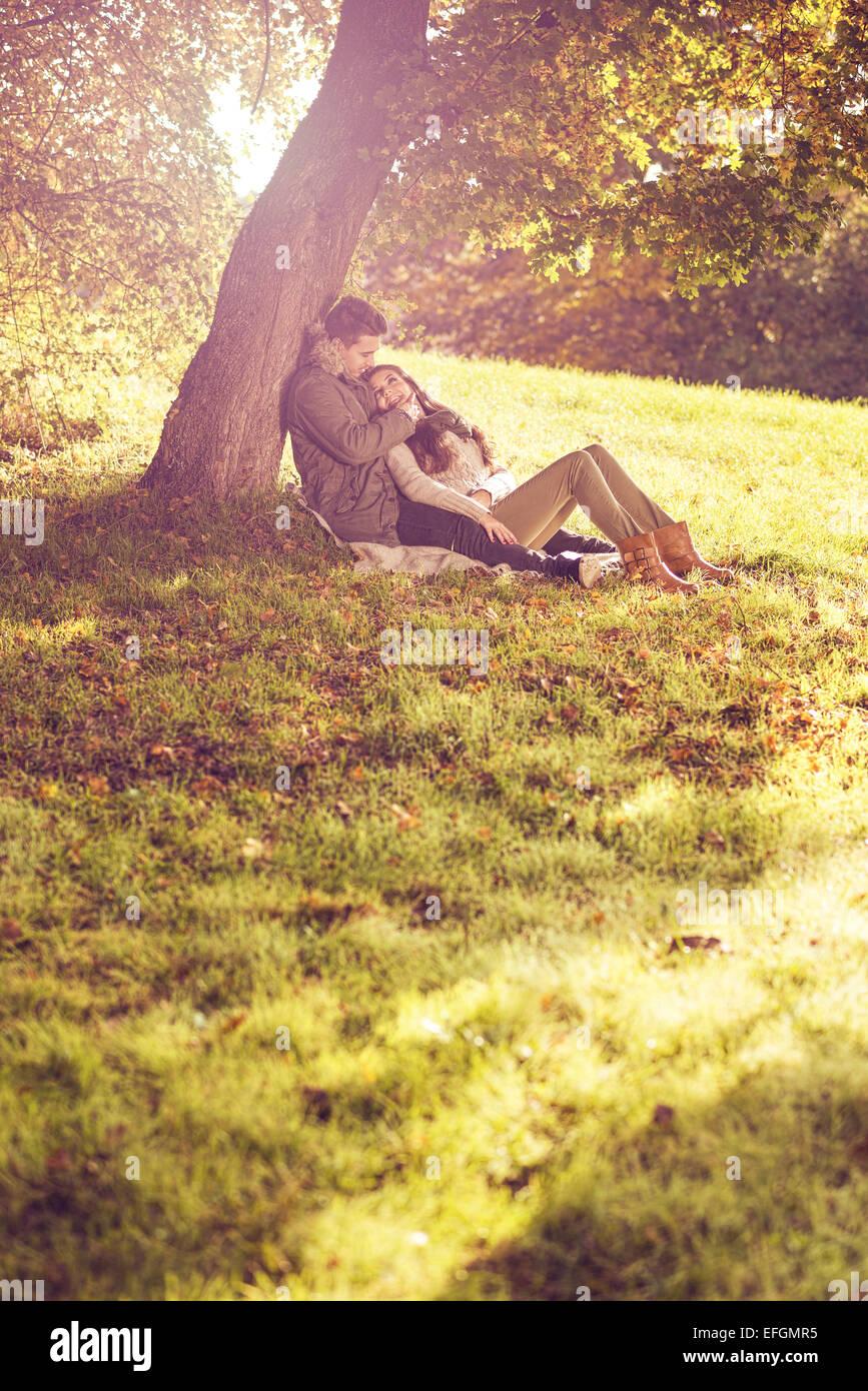 Amore giovane seduto sotto un albero nella pittoresca foresta di autunno Immagini Stock