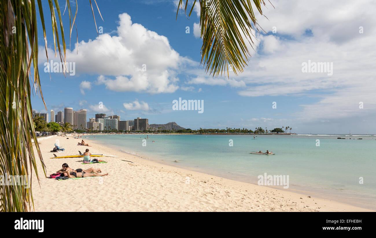 L'Ala Moana Beach Honolulu. Sabbia bianca, un cielo blu e agitando le foglie di palmo impostare la scena su Immagini Stock