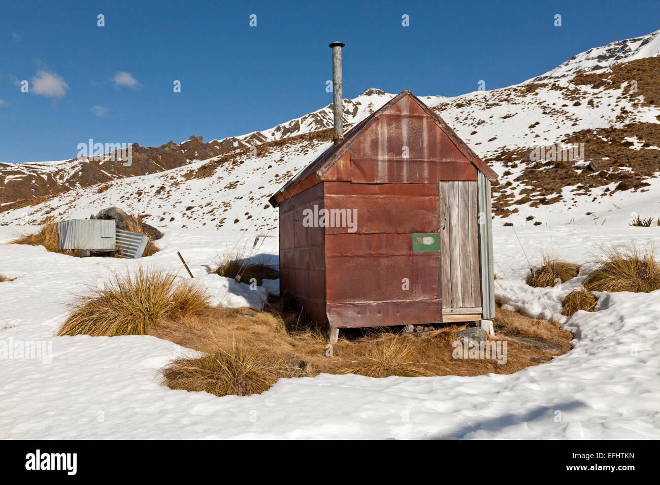 Storico, oro minatore della capanna di ferro nella neve, pionieri baita di montagna, vicino a Queenstown, Isola Immagini Stock