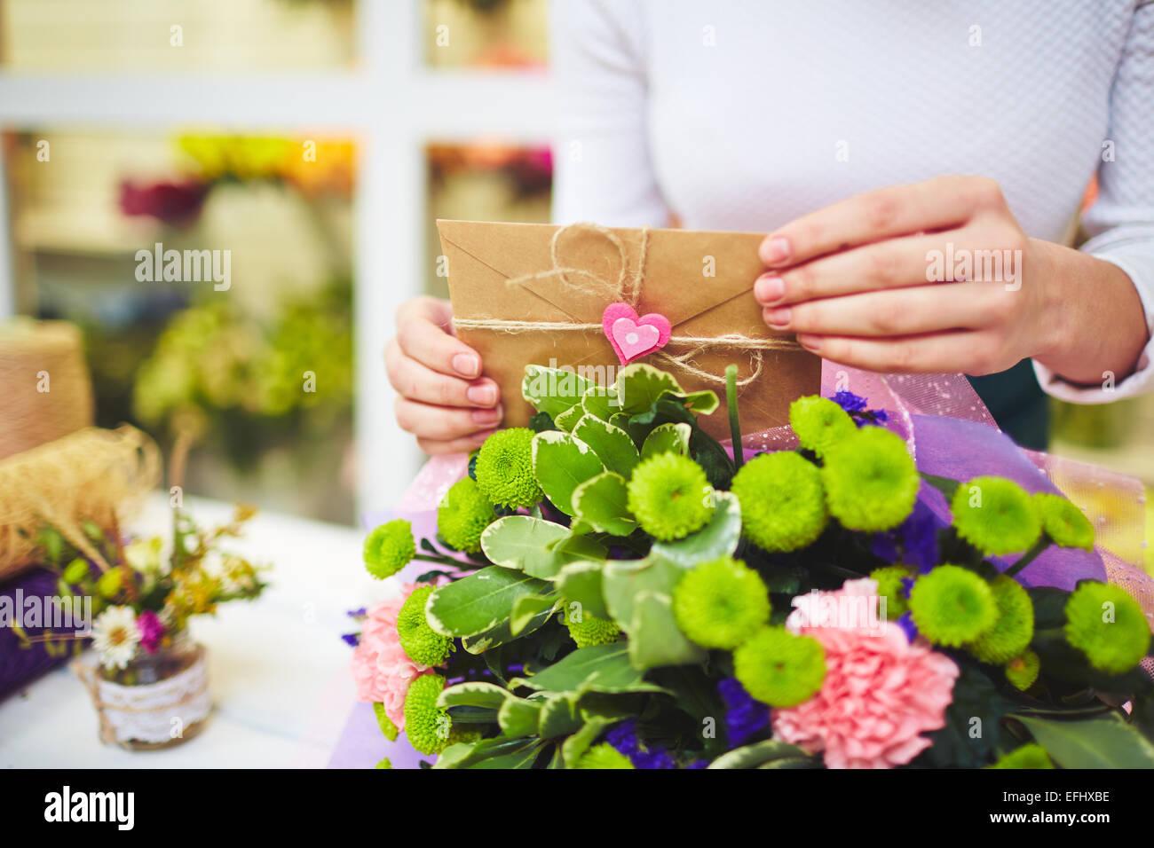 Mani femminili con il messaggio di amore di metterlo in bouquet floreale Immagini Stock