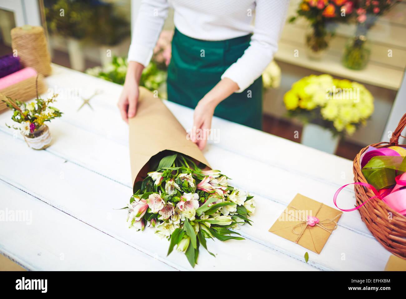 Fiorista femmina vendendo bouquet di amaryllises Immagini Stock
