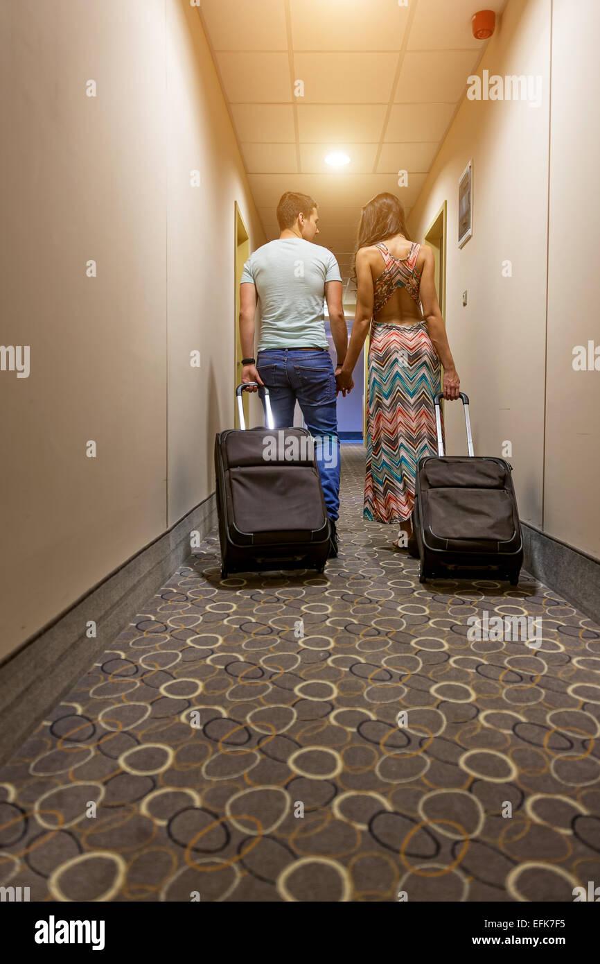 Coppia giovane permanente al corridoio di hotel all'arrivo, cercando per camera, tenendo le valigie. Immagini Stock