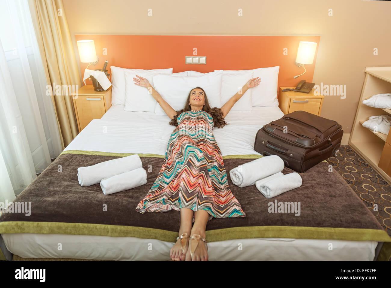 Giovane donna giaceva nel letto di una stanza di un hotel Immagini Stock