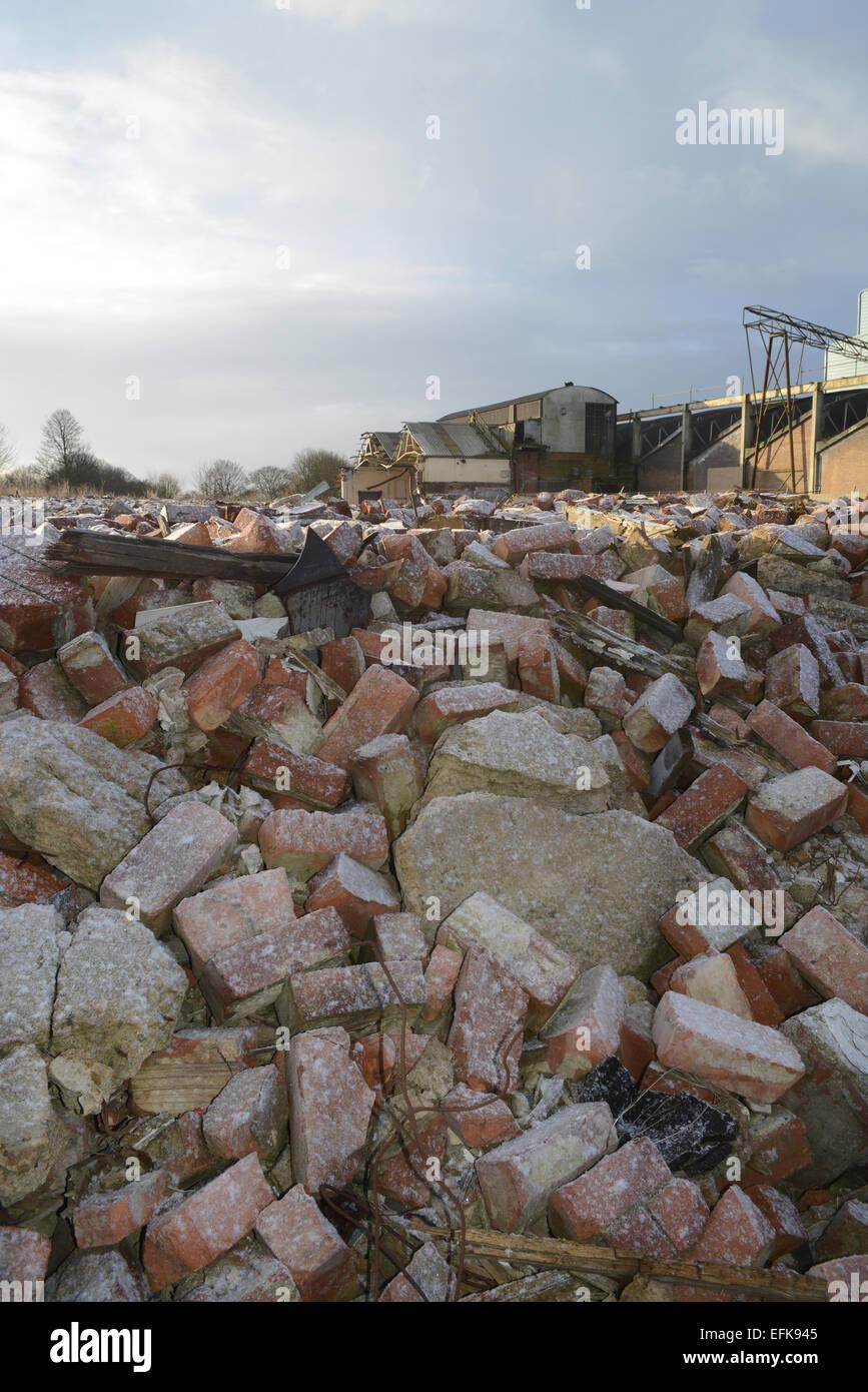 Cumuli di macerie su terreni abbandonati e costruzione di fabbrica coperte da neve invernale vicino a Selby Yorkshire Immagini Stock