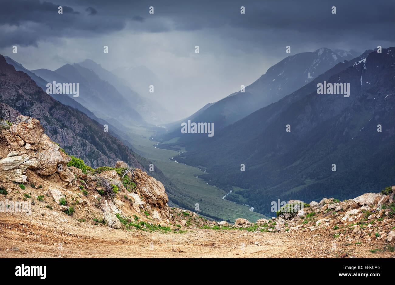 Valle di montagna con il fiume e cucire a sopraggitto cielo grigio in Dzungarian Alatau Kazakistan, in Asia centrale Immagini Stock