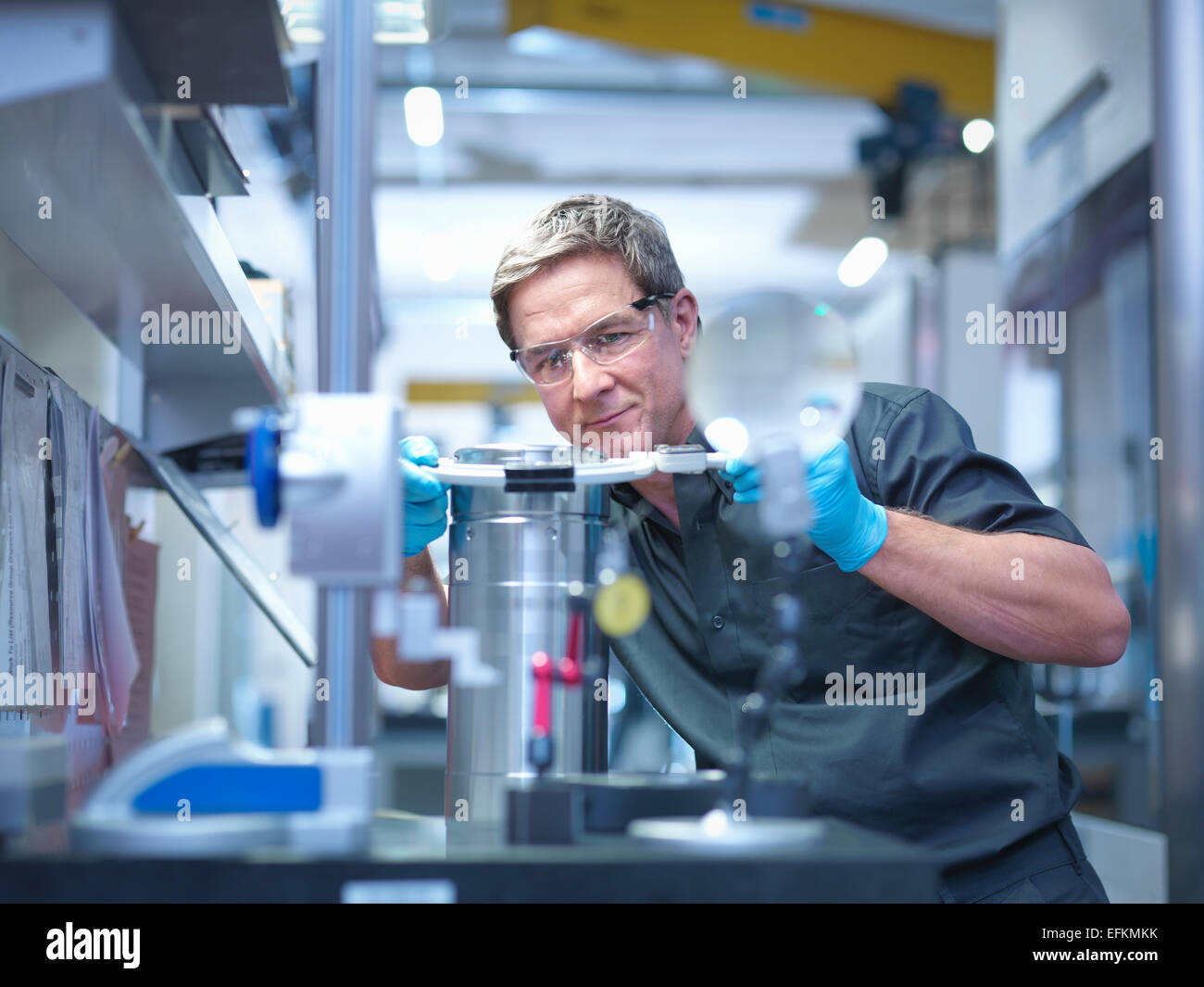 Ingegnere di ispezionare la parte sulla stazione di lavoro in fabbrica di ingegneria Immagini Stock