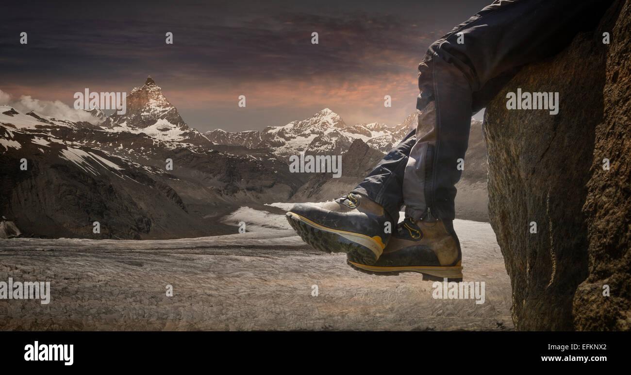 Le gambe dei maschi di scalatore appesa sopra il bordo di roccia, Zermatt e il Cervino, Canton Vallese, Svizzera Immagini Stock