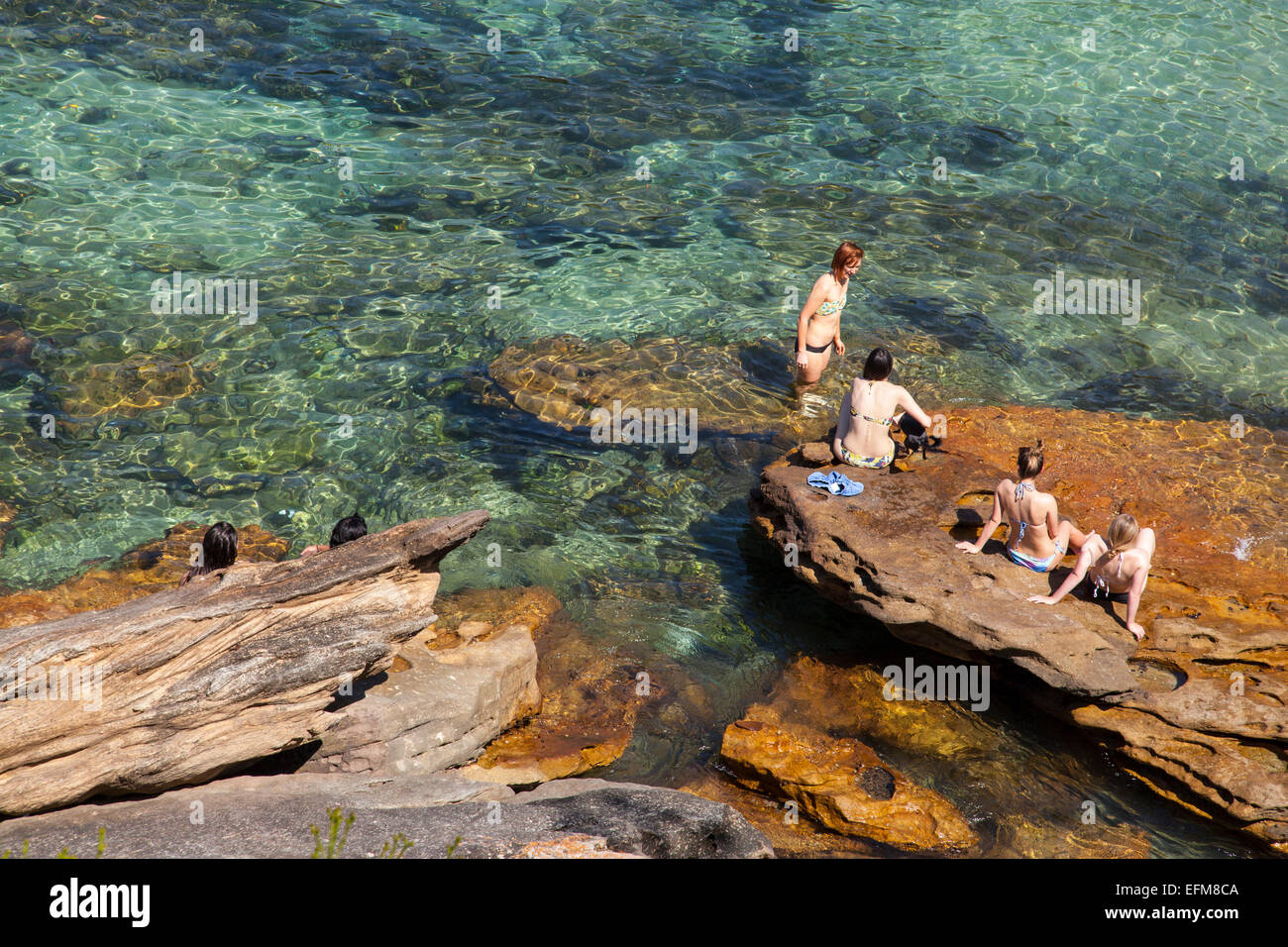 Donna seduta su una roccia a Gordon's Bay, Sydney, Australia Immagini Stock