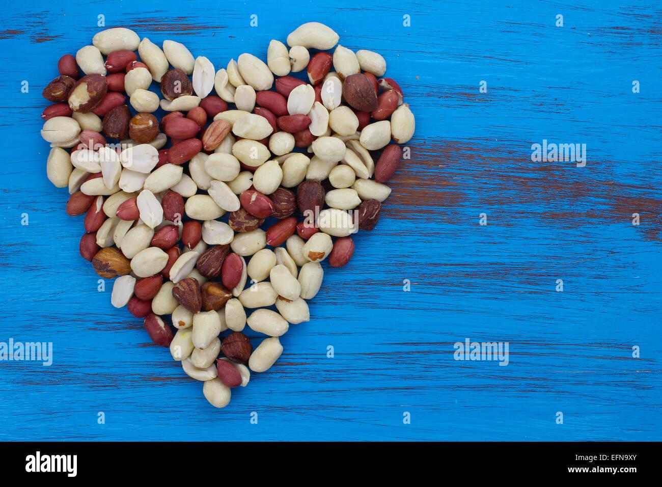 I dadi di arachidi in una forma di cuore su blu rustico in legno invecchiato sfondo. Immagini Stock