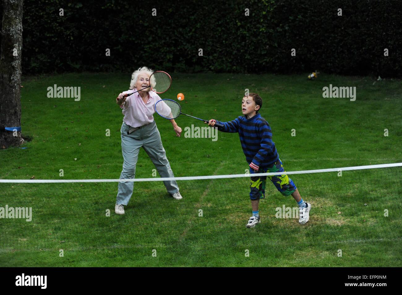 Nonni giocare Badminton con il loro nipote nel loro giardino nel North Yorkshire. Inghilterra Regno Unito Immagini Stock