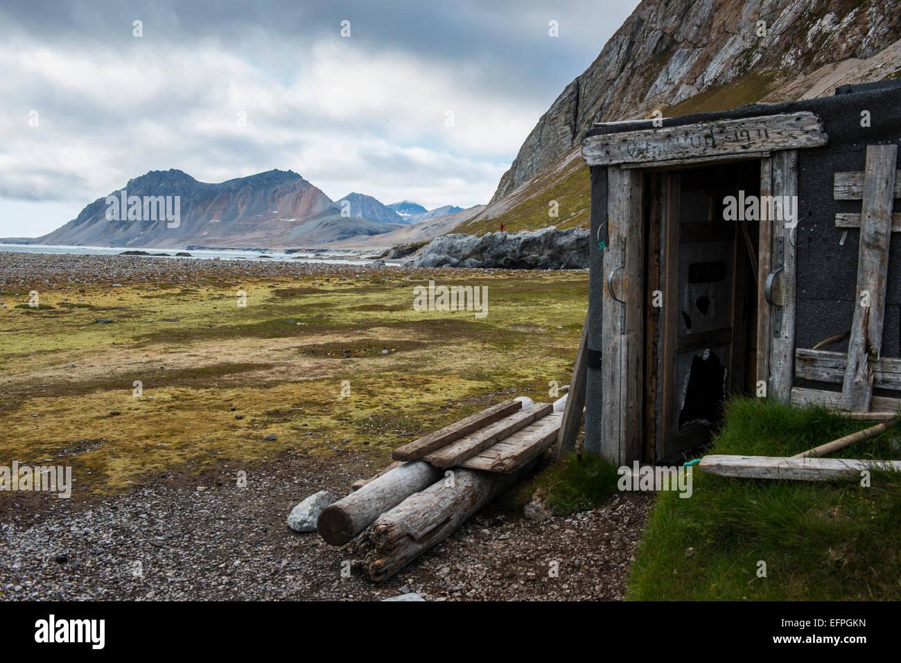 Capanna abbandonata su Alkhornet con una enorme roccia in background, Svalbard, Arctic Immagini Stock