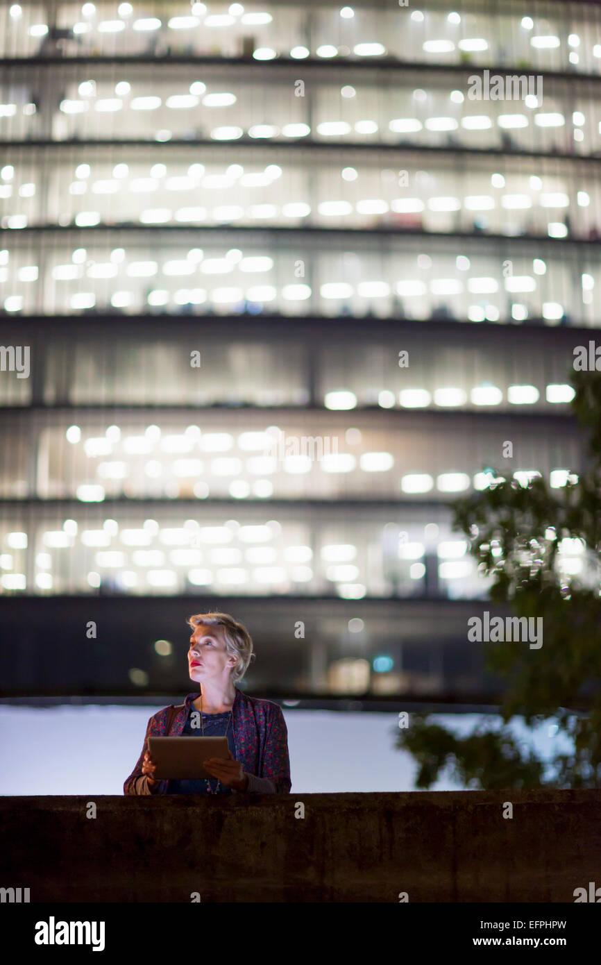 Coppia imprenditrice utilizzando tavoletta digitale di fronte all edificio per uffici di notte, Londra, Regno Unito Immagini Stock