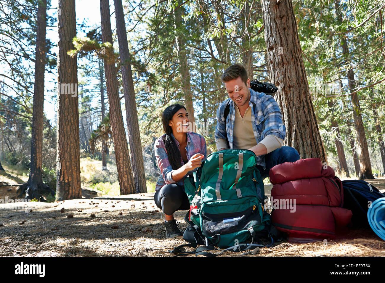 Coppia giovane disimballaggio camping zaino in foresta, Los Angeles, California, Stati Uniti d'America Immagini Stock