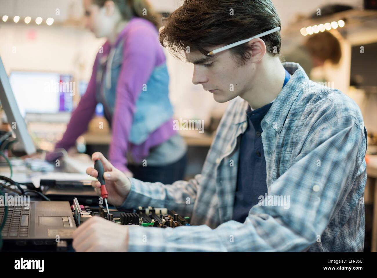 Due persone in un computer repair shop. I tecnici, i giovani al lavoro per riparare il computer. Immagini Stock