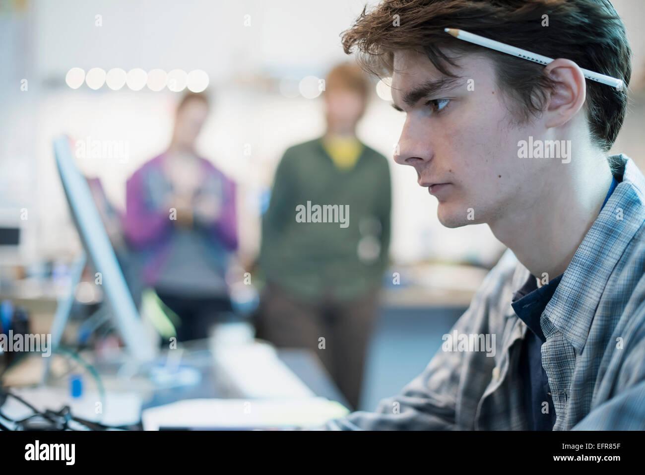 Un giovane uomo seduto a un computer in un negozio di riparazione. Due persone in background. Immagini Stock
