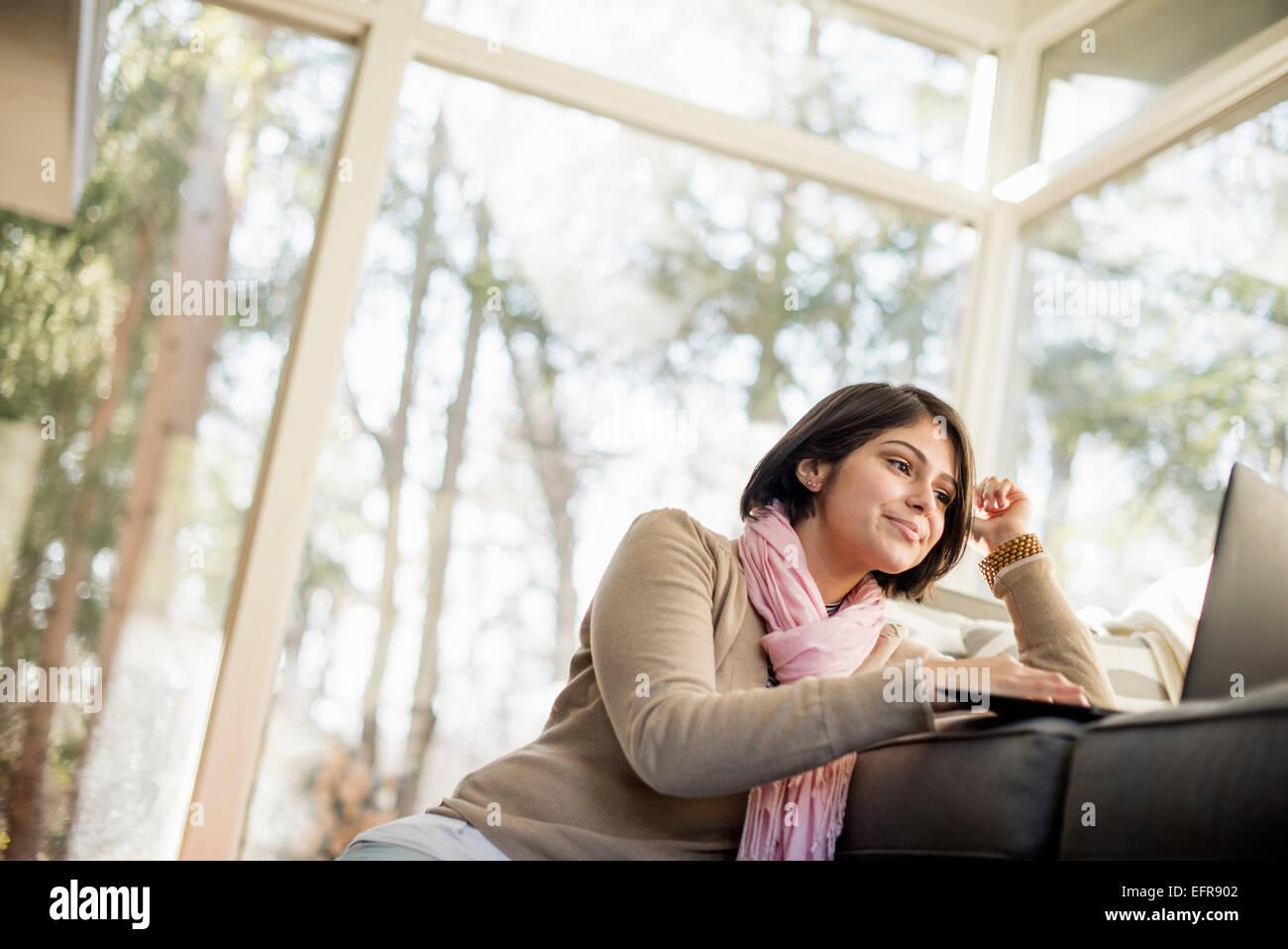 Donna seduta sul pavimento nella parte anteriore del divano guardando il suo computer portatile. Immagini Stock