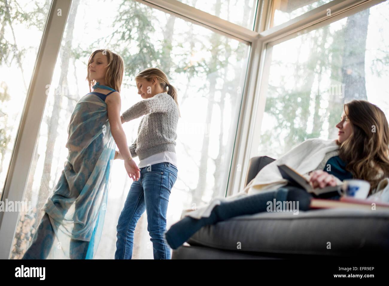 Due ragazze in piedi in un salotto, vestirsi, una donna seduta su un divano, guardando. Immagini Stock