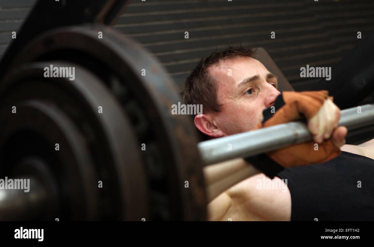 Bodybuilding allenamento in palestra. Maschio di sollevamento pesi gratuiti di formazione utilizzando pecks barbell. Immagini Stock