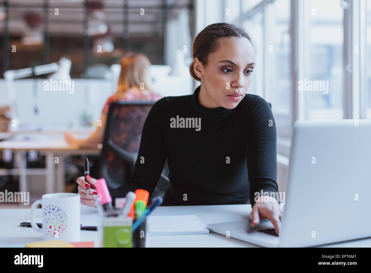 Immagine della giovane donna che lavorano su computer portatile mentre è seduto alla sua scrivania in ufficio Immagini Stock