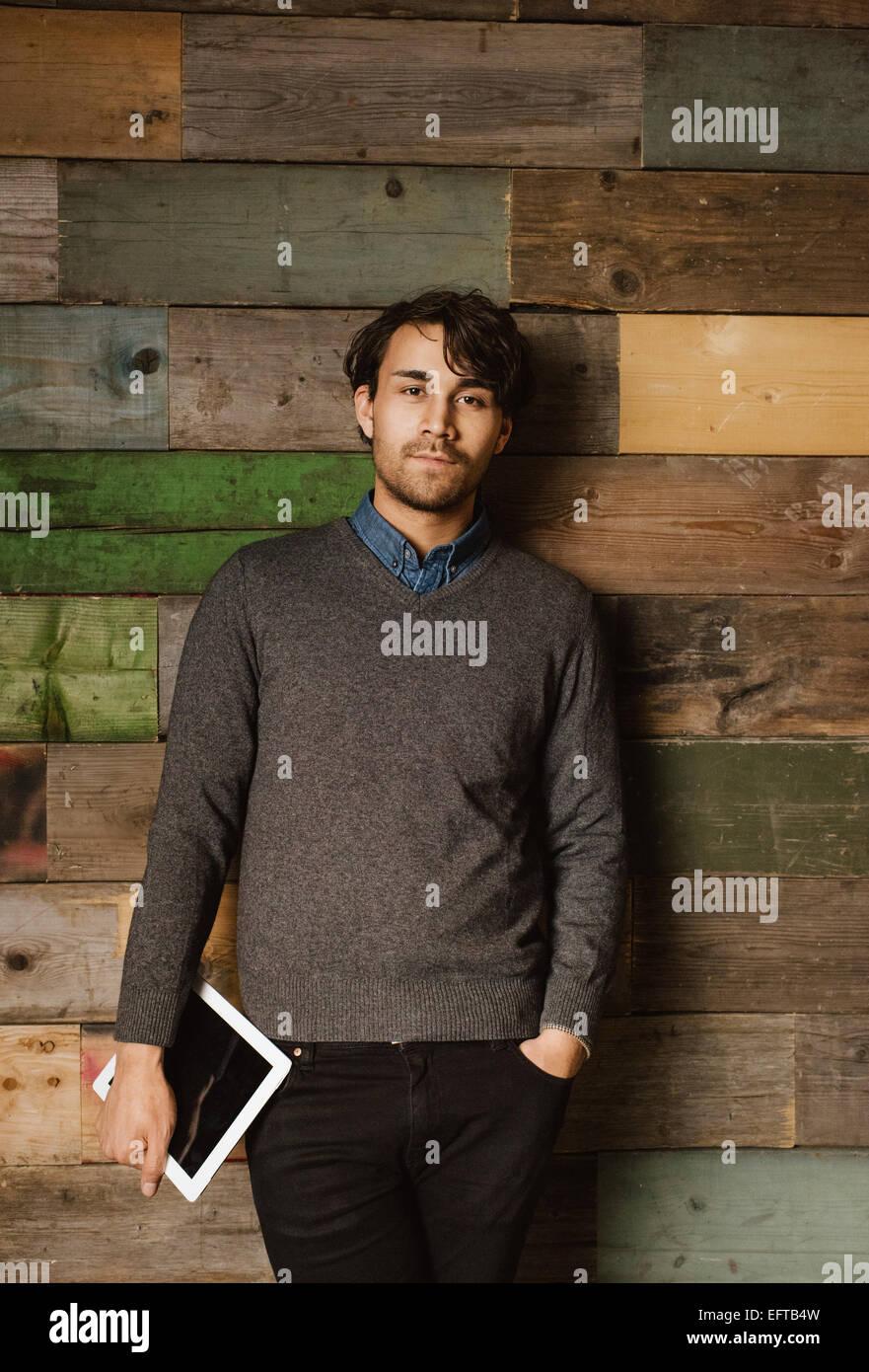 Ritratto di giovane imprenditore con una tavoletta digitale in piedi contro una parete in legno. Bel giovane esecutivo Immagini Stock