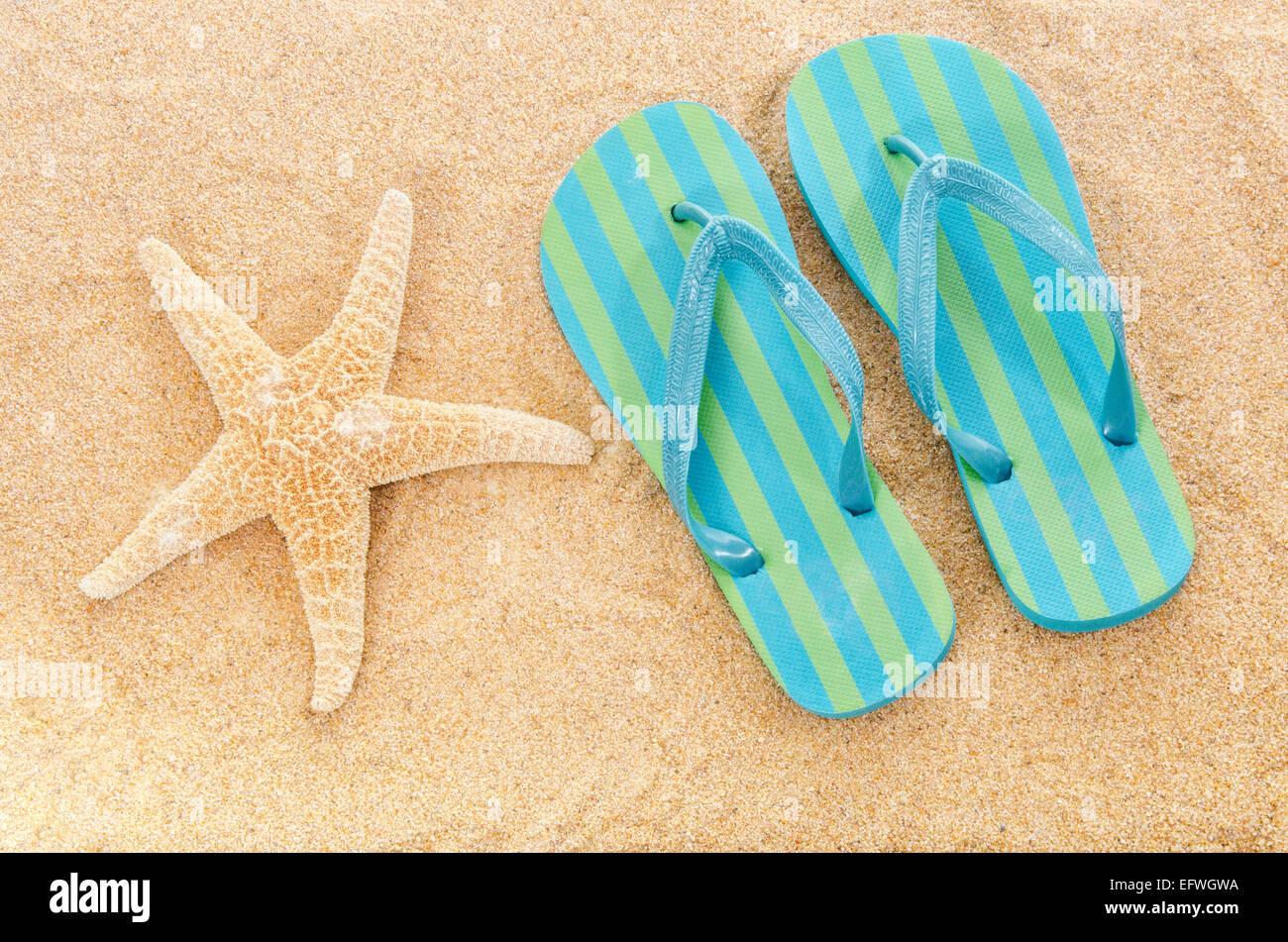 Striped flip flop sandali di gomma ciabatte sulla spiaggia sabbiosa stella di mare Stella di mare estate vacanze Foto Stock