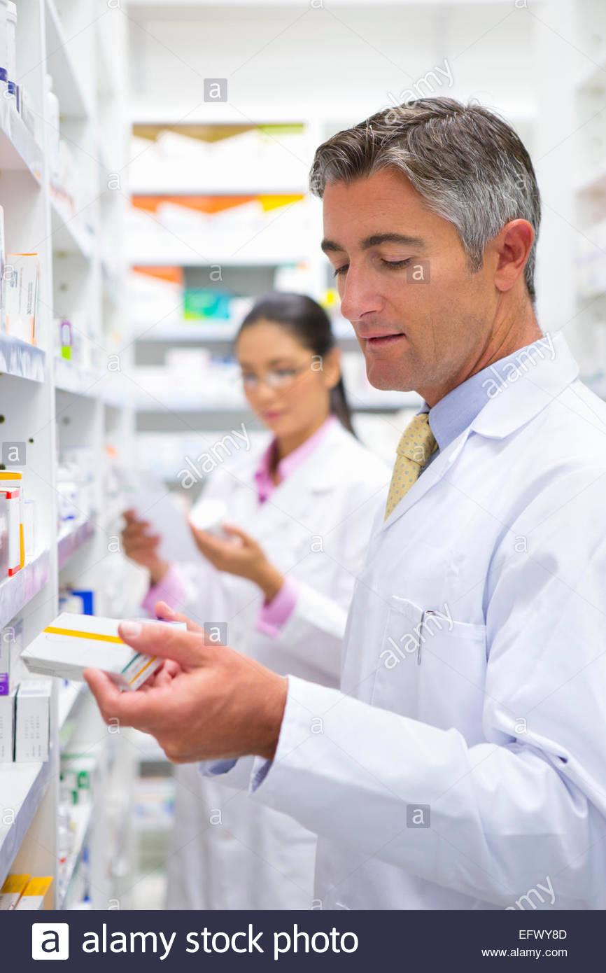 Farmacisti lettura pack di medicina da farmacia ripiano Immagini Stock