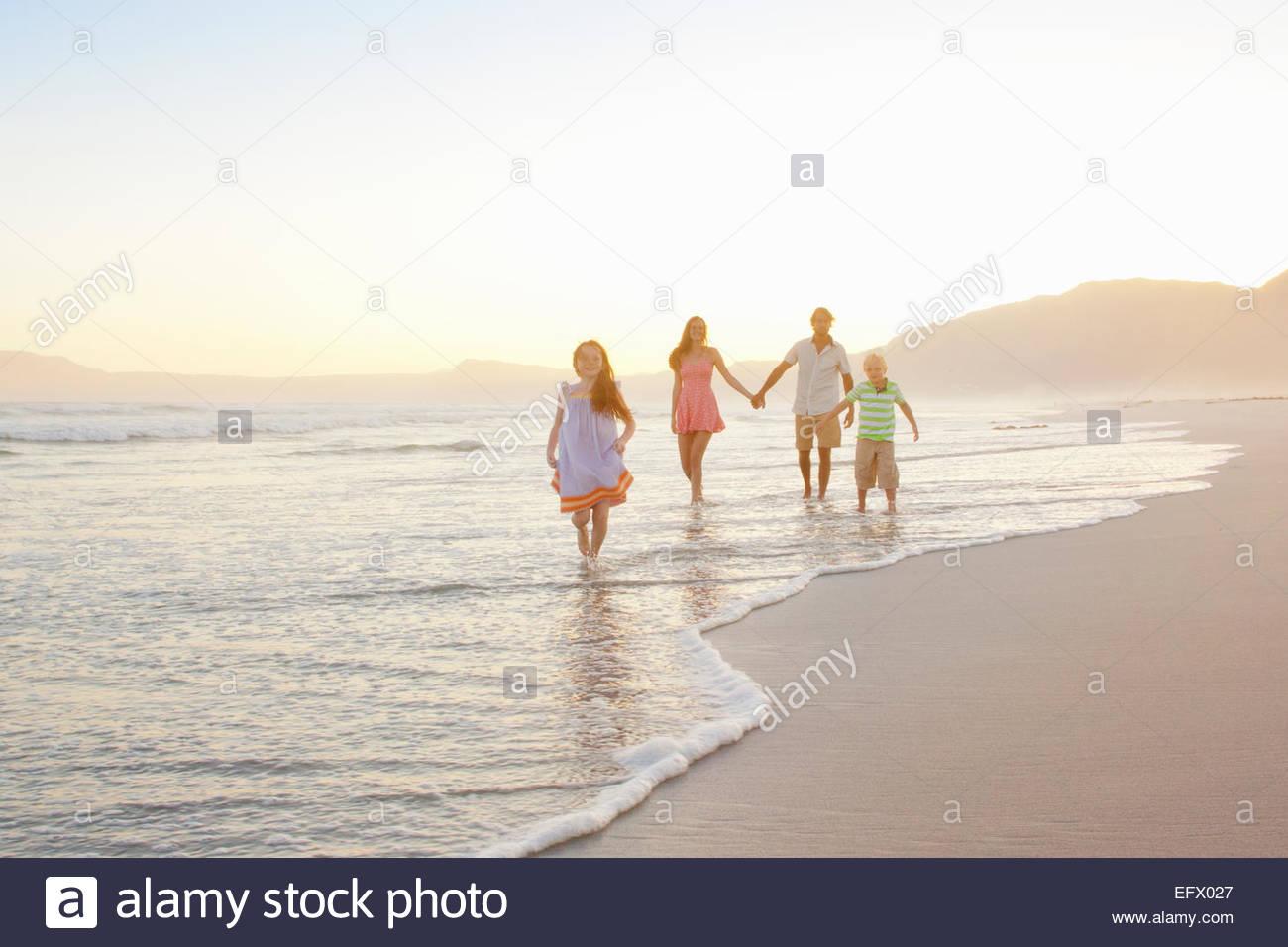La famiglia felice tenendo le mani sul sunny beach Immagini Stock