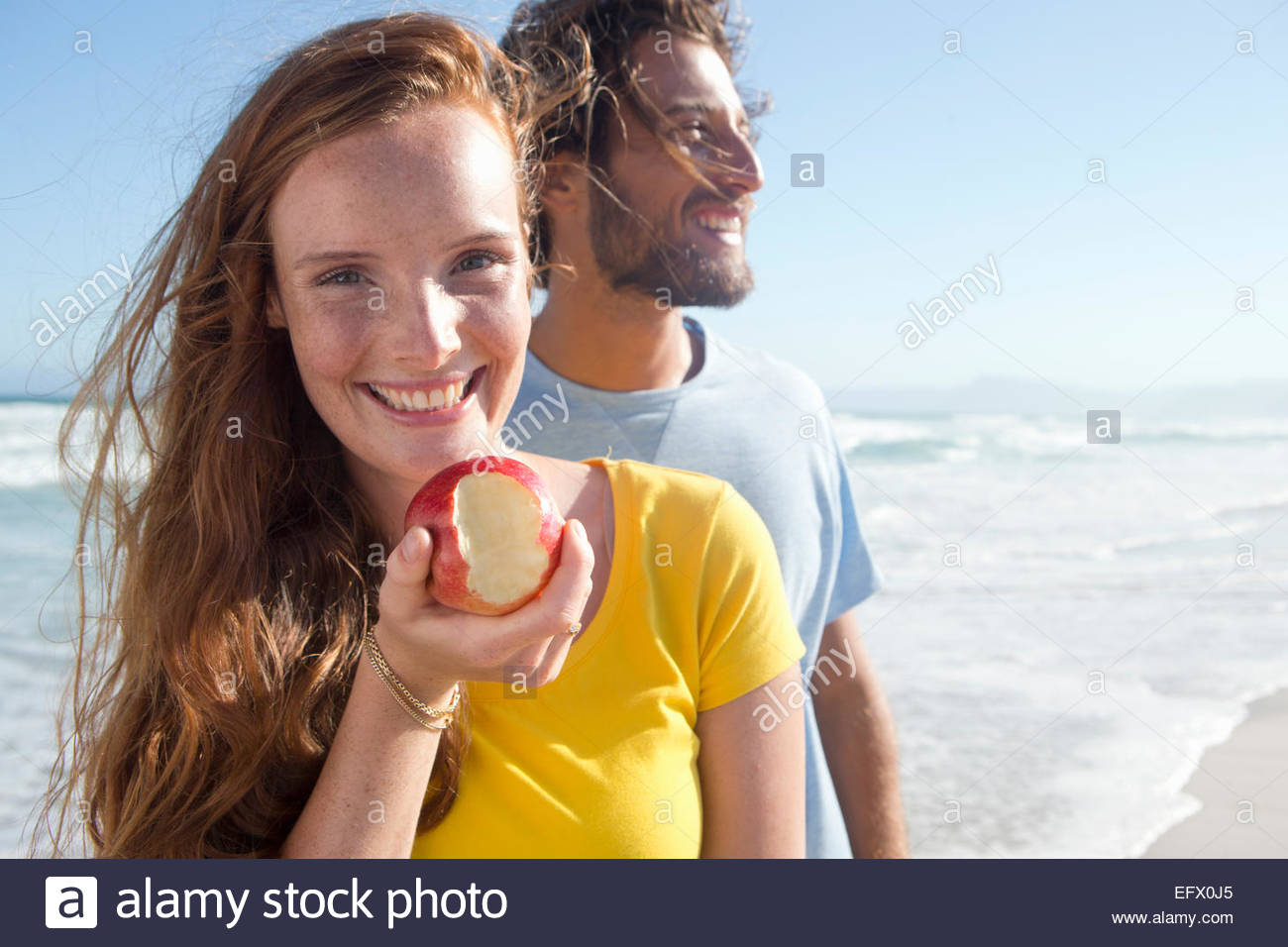 Coppia sorridente di sunny beach, con la donna in possesso di un Apple con un boccone fuori di essa Immagini Stock