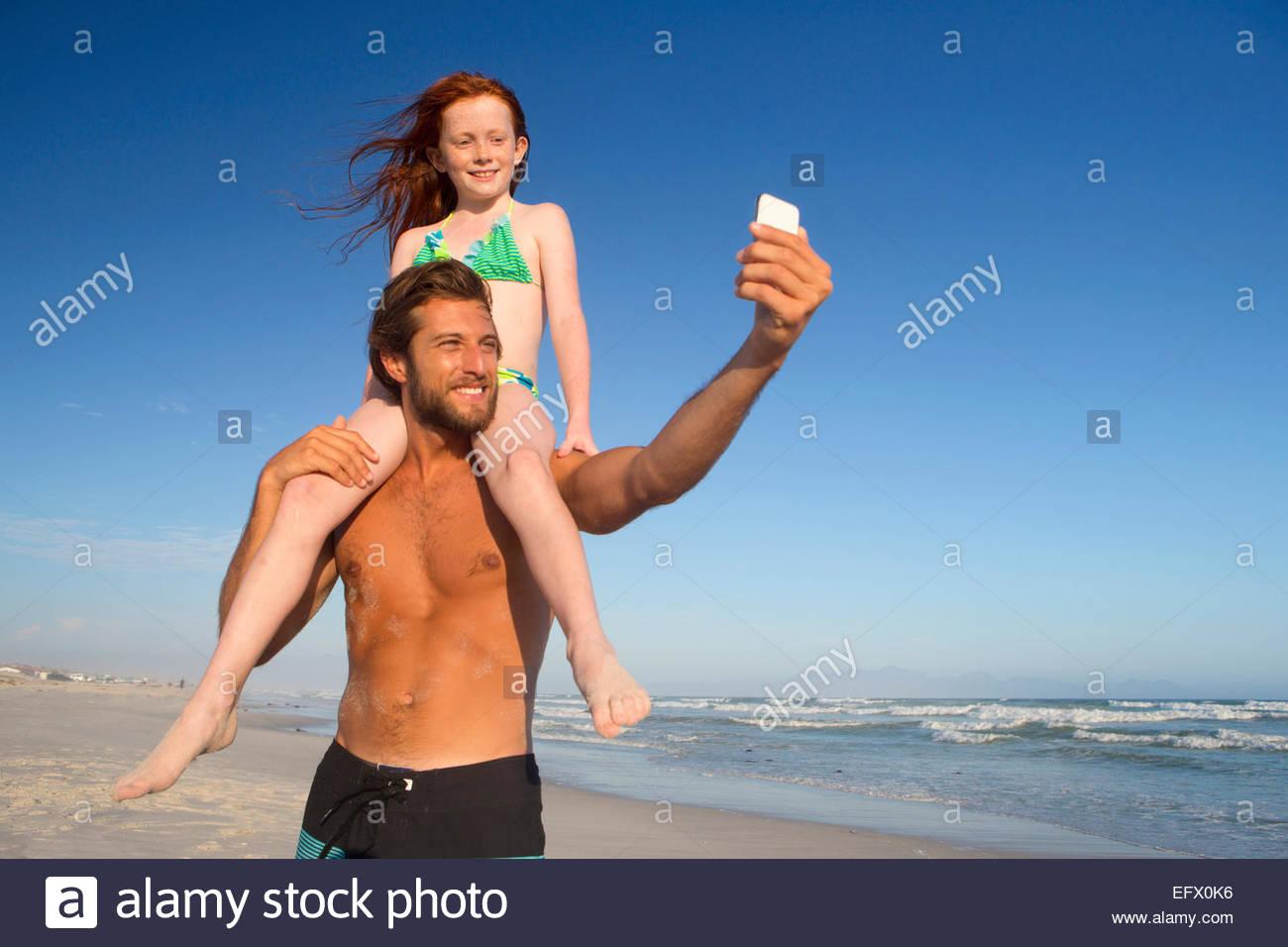 Padre e figlia con seduta sulle spalle, tenendo selfie di sunny beach Immagini Stock