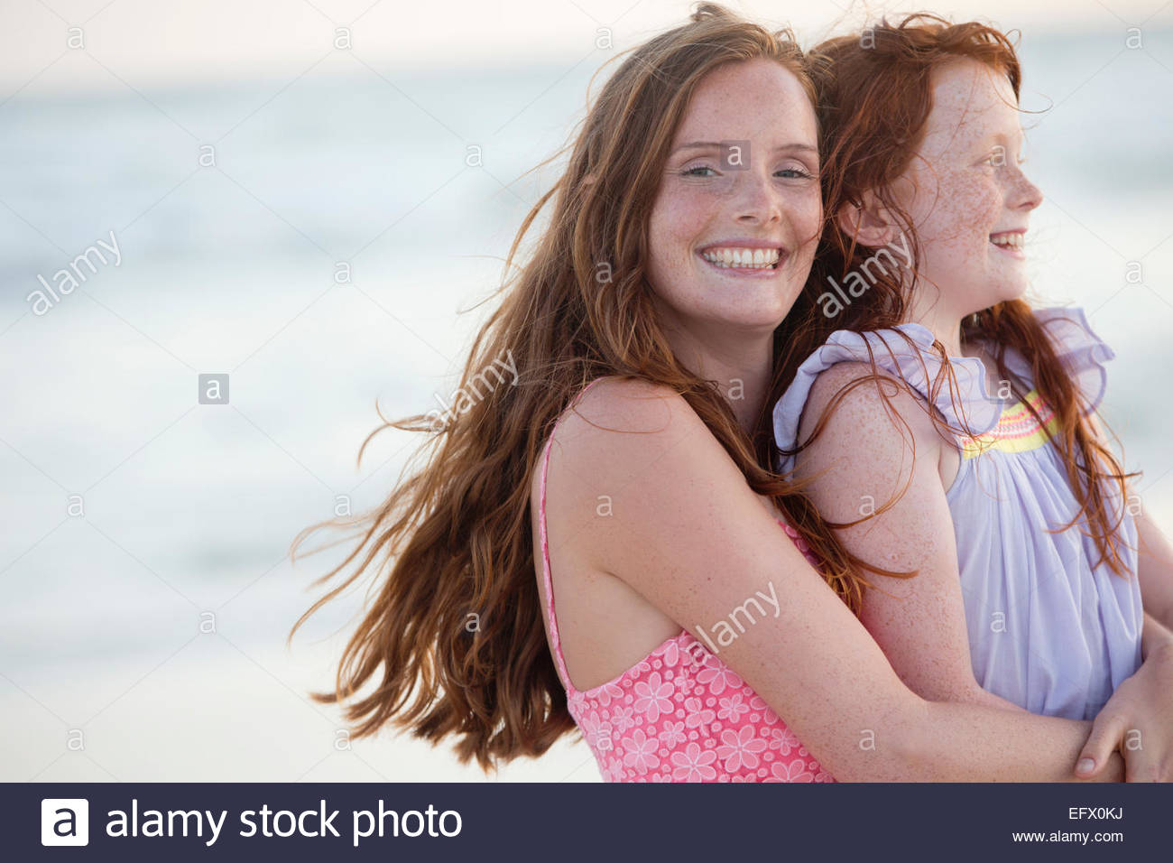 Ritratto di Madre e figlia, sorridente alla fotocamera, abbracciando di sunny beach Immagini Stock