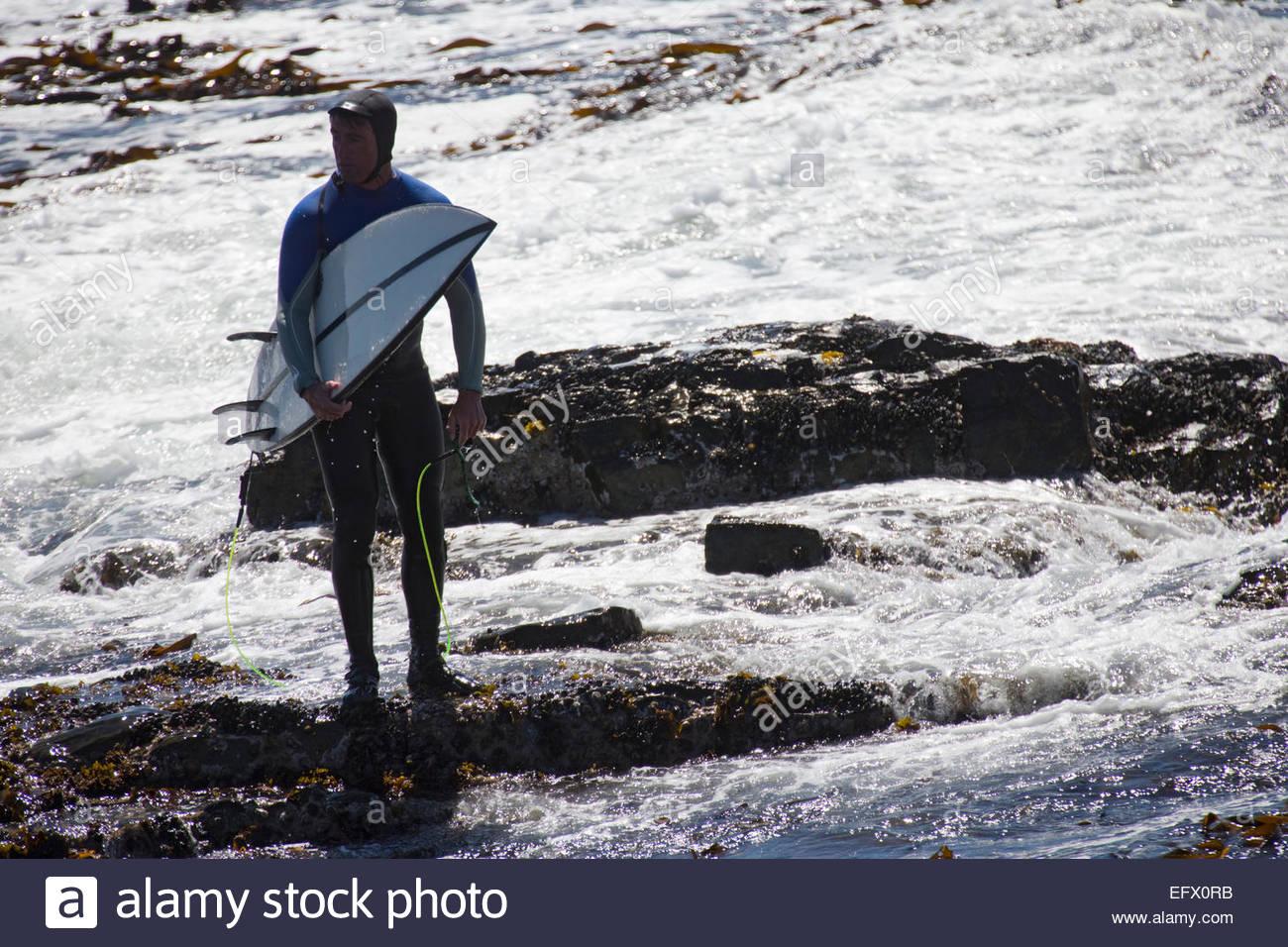 Uomo con la tavola da surf in piedi sulle rocce Immagini Stock