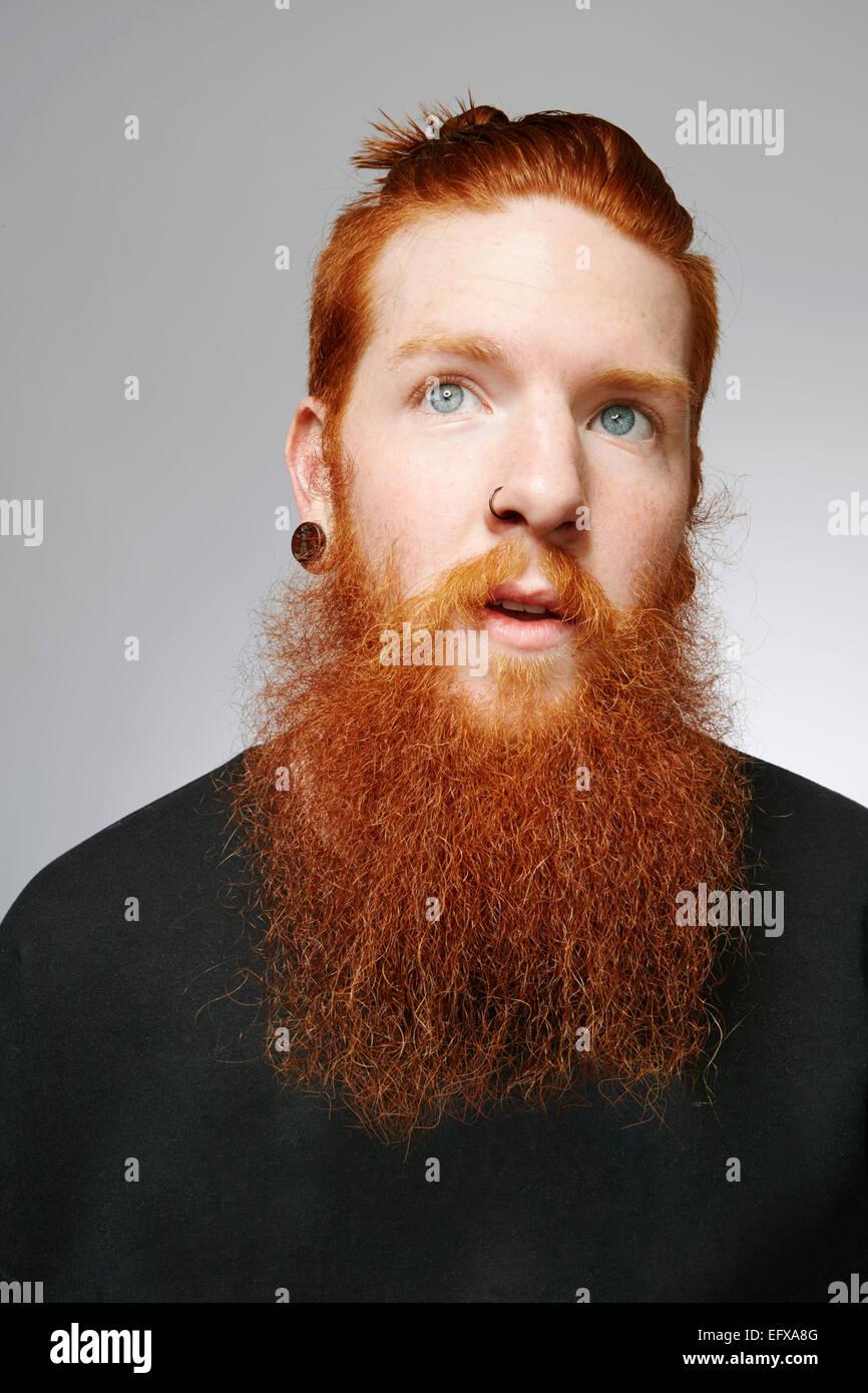 Studio Ritratto di giovane uomo con gli occhi blu, rosso di capelli e barba sovradimensionate Immagini Stock