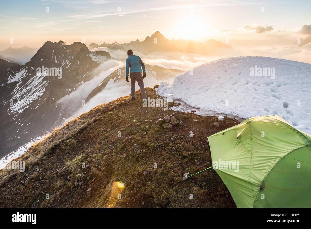 Giovane maschio camper guardando a vista, Alpi Bavaresi, Oberstdorf, Baviera, Germania Foto Stock