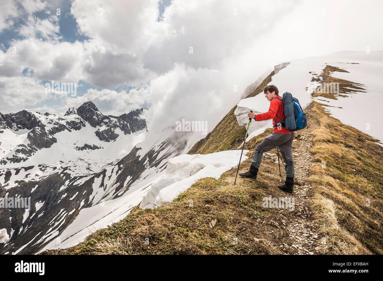 Giovane maschio trekker montagna cercando di ridge nelle Alpi Bavaresi, Oberstdorf, Baviera, Germania Immagini Stock