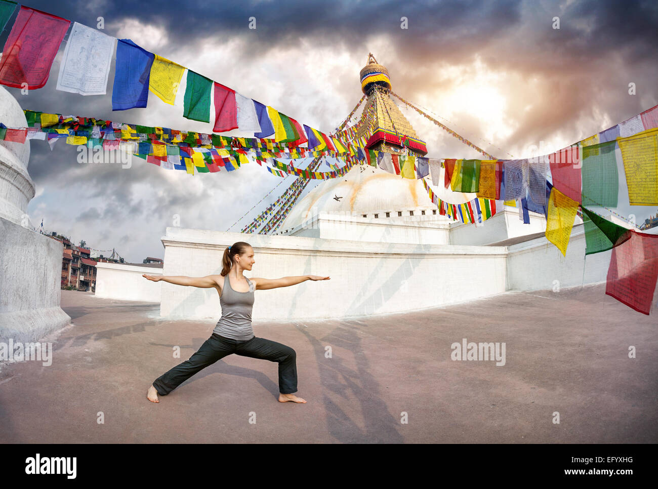 Donna fare yoga warrior pongono a Bodnath stupa, Kathmandu, Nepal Foto Stock