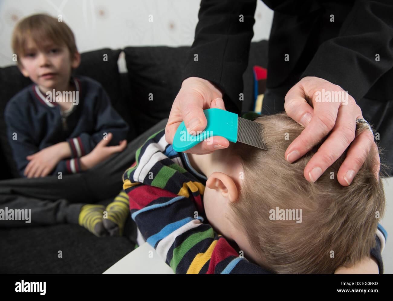 Madre controllo childs testa per i pidocchi con un pettine Foto Stock
