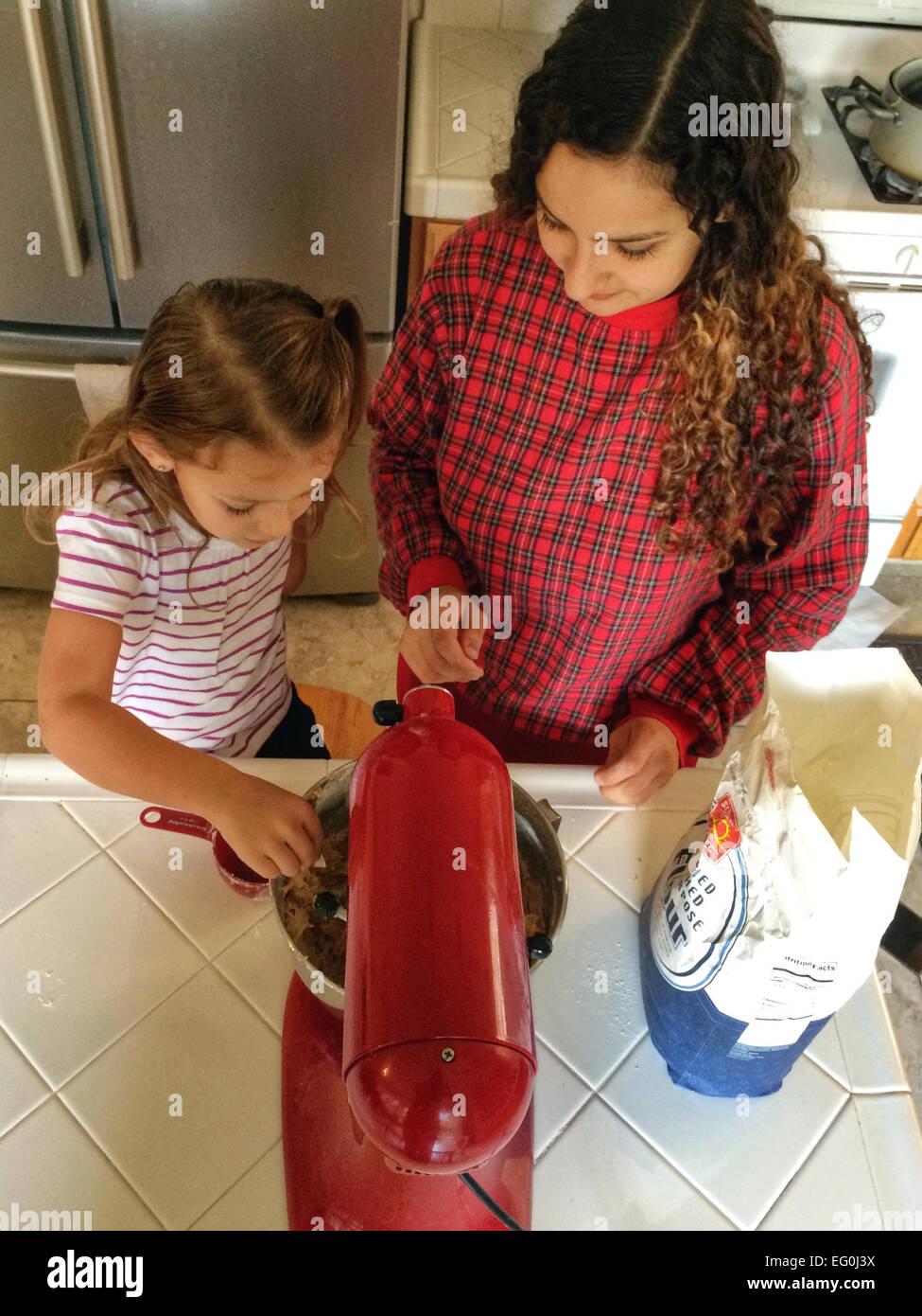 La ragazza (4-5) la cottura con la sua mamma Immagini Stock