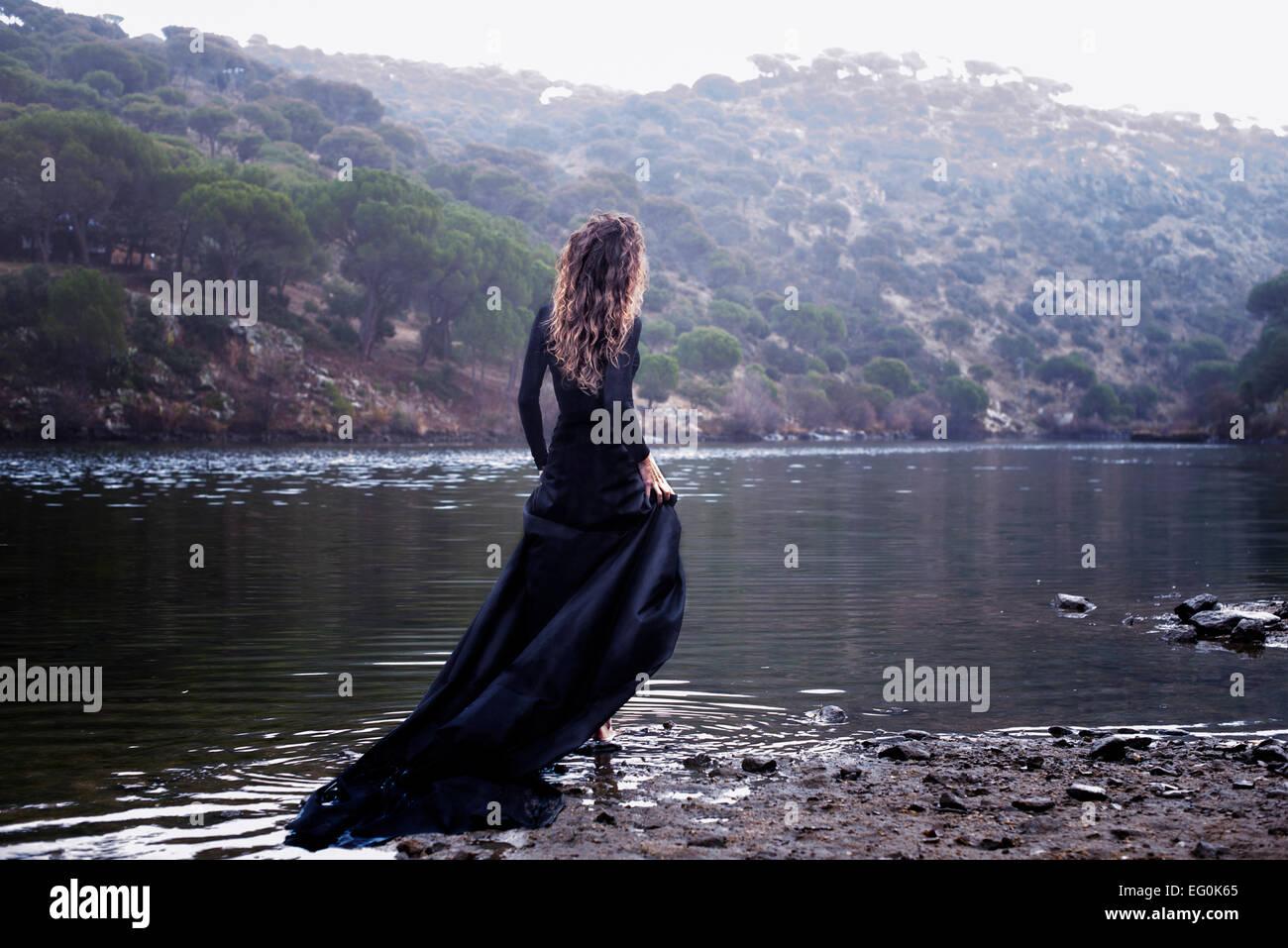 Donna in abito nero a piedi in acqua Immagini Stock