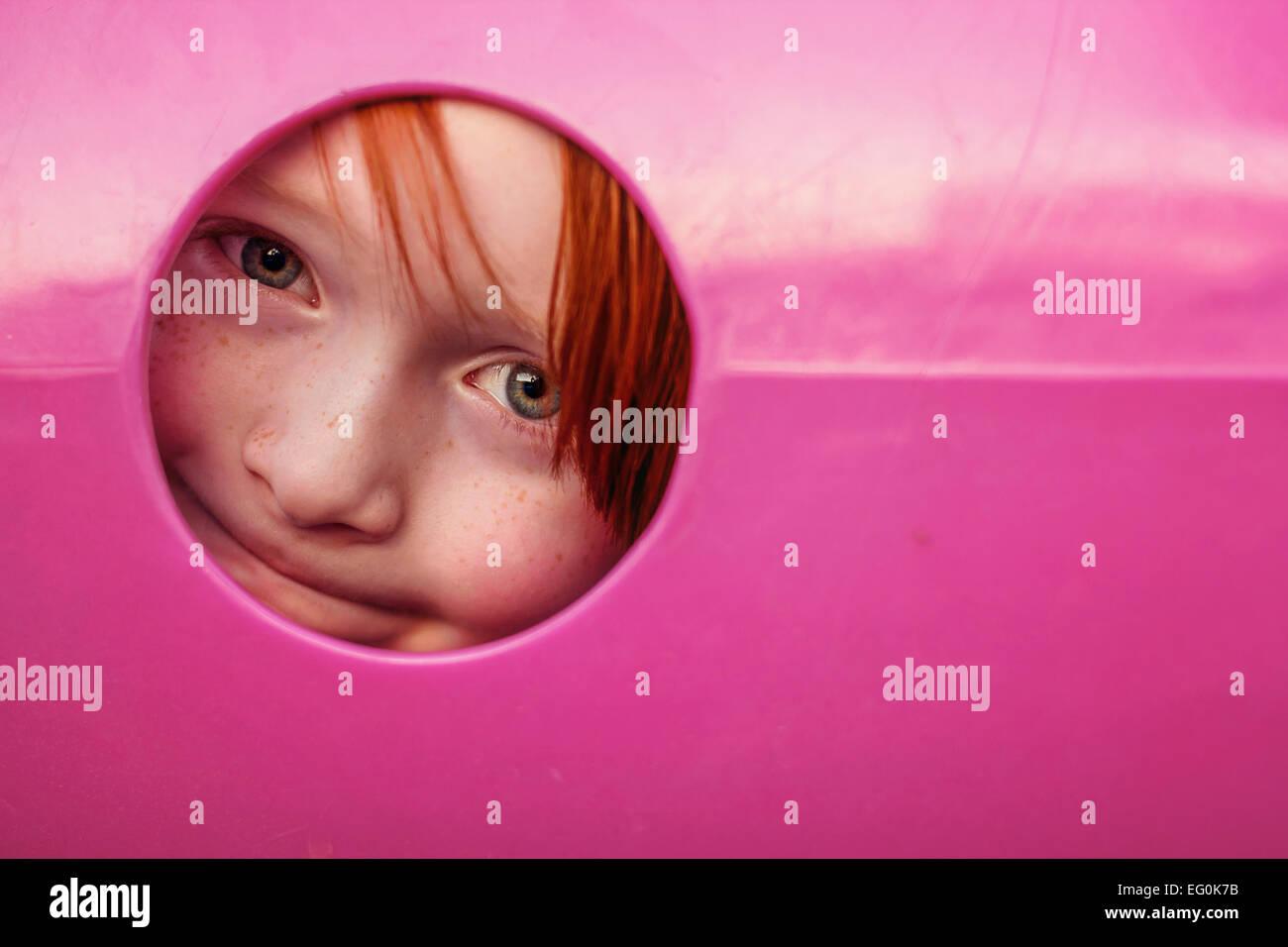 Ragazzo giovane spiata attraverso il foro nel tunnel di giochi per bambini Immagini Stock