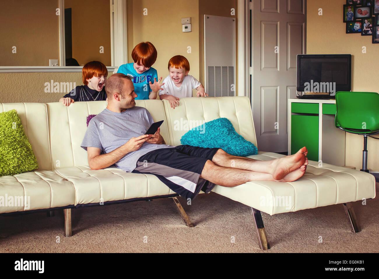 Tre ragazzi salta fuori da dietro un lettino a sorpresa il loro padre Immagini Stock