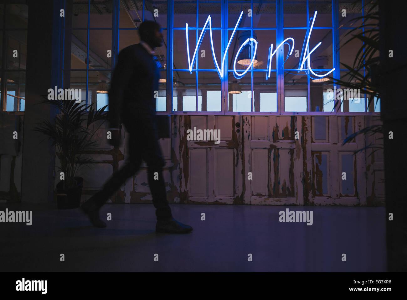 Corridoio di un ufficio moderno con un giovane uomo che cammina da. Grande luce al neon segno di lavoro. Immagini Stock