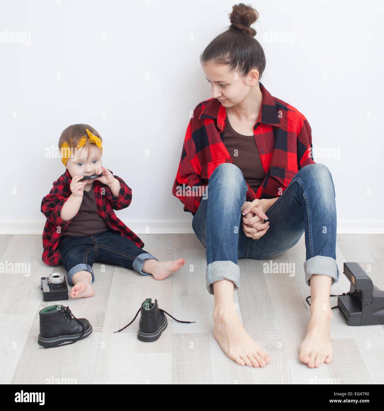La madre e il bambino in rosso a scacchi camicie e jeans Immagini Stock