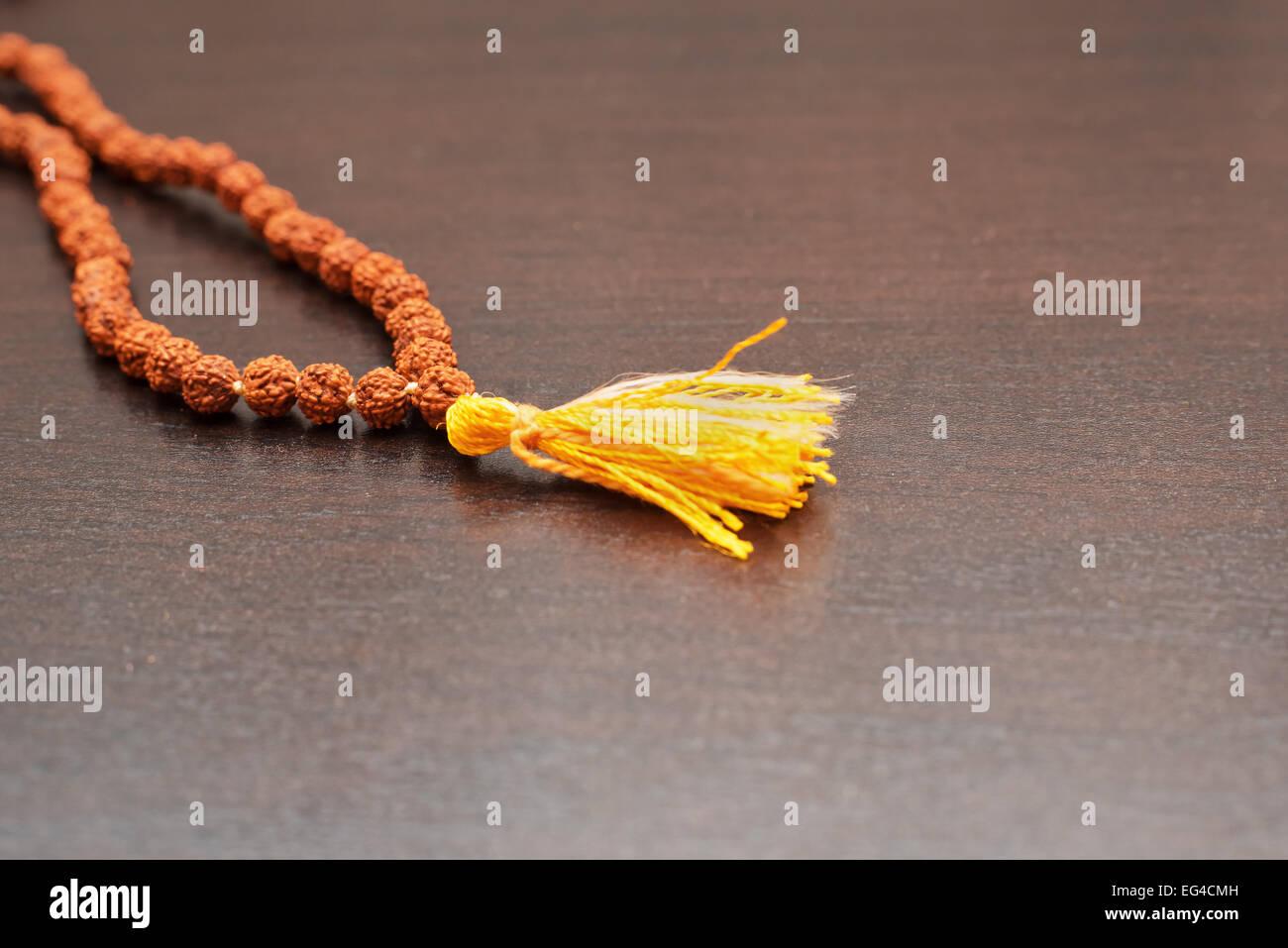 Japa mala sul tavolo. Preghiera talloni realizzati dai semi dell'albero rudraksha Foto Stock