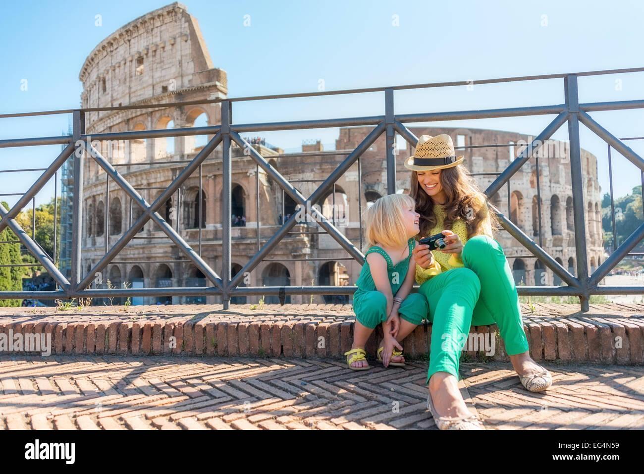 La madre e il bambino ragazza seduta davanti al Colosseo a Roma, Italia Foto Stock